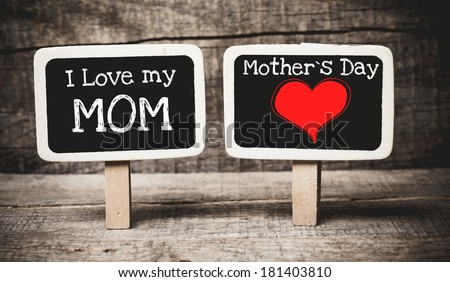 I love my mom and mother day phrase handwritten on the school blackboards on wood background - stock photo
