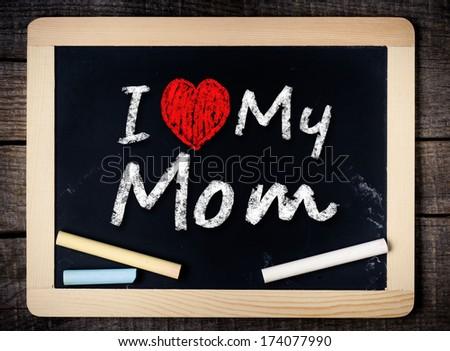 I love my mom phrase handwritten on the school blackboard on wood background - stock photo