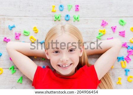 I love my mom! Top view of cute little girl holding hands behind head while lying on the floor with plastic colorful letters laying around her - stock photo