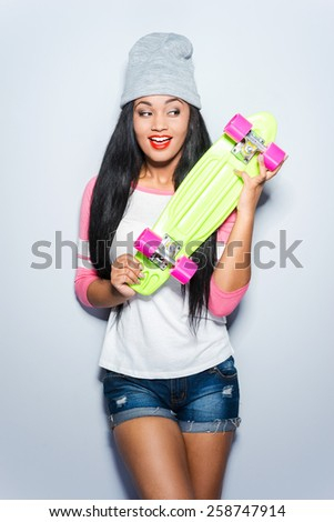 I love my new skateboard! Happy young African woman in funky clothes holding colorful skateboard and looking at it with smile while standing against grey background  - stock photo