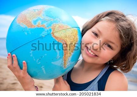 I love my world! Young girl hugs Earth globe - stock photo