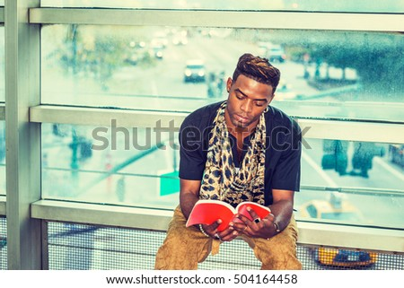 I Love Reading. Dressing fashionably, African American Man sits against glass wall on campus in New York, looking down, reading red book. Street, many cars on background. Filtered look.