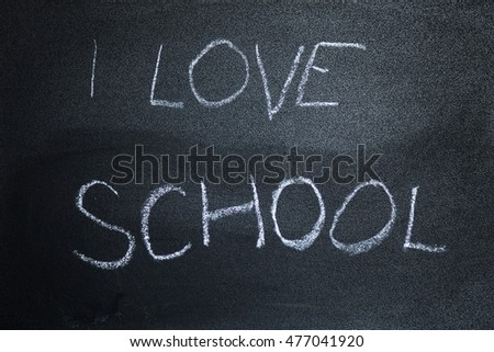 i love school message written on a chalkboard in kids writing. symbolizing love for knowledge