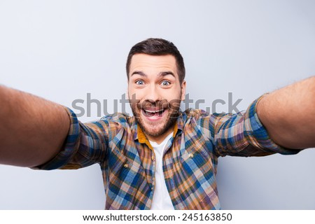 I love selfie! Handsome young man in shirt holding camera and making selfie and smiling while standing against grey background - stock photo
