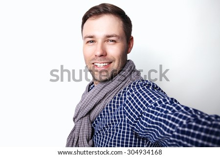 I love selfie! Handsome young man in shirt holding camera and making selfie and smiling while standing against white background - stock photo