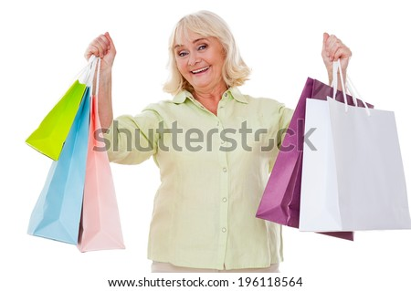 I love shopping! Happy senior woman stretching out hands with shopping bags and smiling while standing isolated on white background - stock photo
