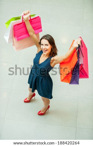 I love shopping! Top view of beautiful young woman holding shopping bags and smiling at camera - stock photo
