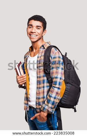 I love studying. Handsome young Afro-American student holding books and smiling while standing against grey background - stock photo