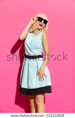 I love summer sun. Smiling elegance young woman in sunglasses looking at the sun. Three quarter length studio shot on pink background. - stock photo