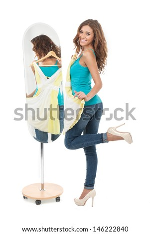 I love this dress! Happy young women holding a dress while standing in front of the mirror and looking at camera - stock photo