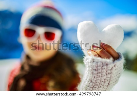 I love winter. Happy winter girl wearing knitted wear scarf. Excited beautiful smiling teenager playing with snowball in heart shape.