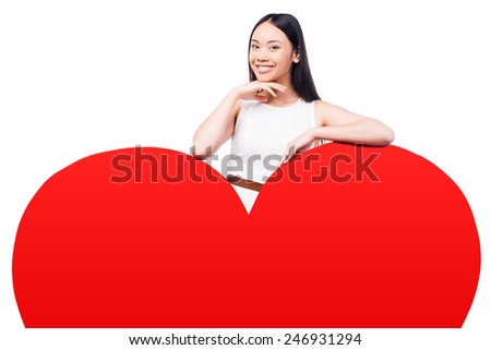 I love you as much! Beautiful young Asian woman in pretty dress looking at camera leaning on huge heart shaped valentine card and smiling while standing against white background   - stock photo