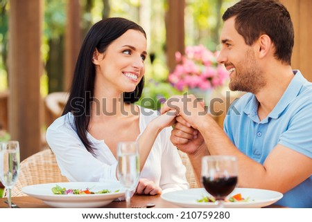 I love you! Beautiful young loving couple holding hands and looking at each other while relaxing in outdoors restaurant together  - stock photo
