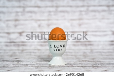 I Love You egg cup with a farm fresh brown boiled hens egg for a sentimental breakfast greeting on rustic grey wood background with copyspace - stock photo