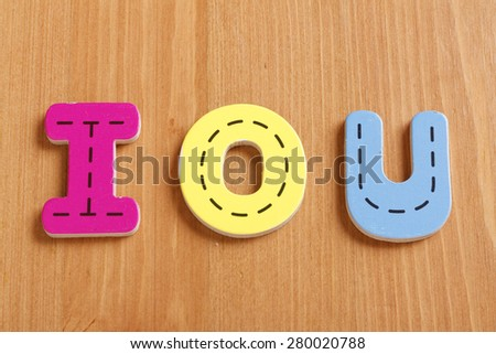 I LOVE YOU, IOU,spell by woody puzzle letters with woody background - stock photo
