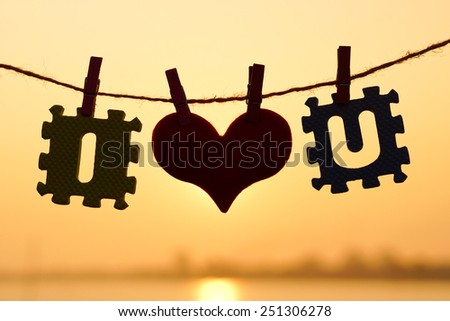 I love you - Jigsaws with letter I and U hung on the rope with a red heart - Love for Valentine's day - stock photo