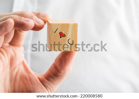 I Love You message on a wooden block with a hand-drawn red heart and text depicting relationships, love, romance, affection and commitment, mans hand over a white shirt with copyspace. - stock photo