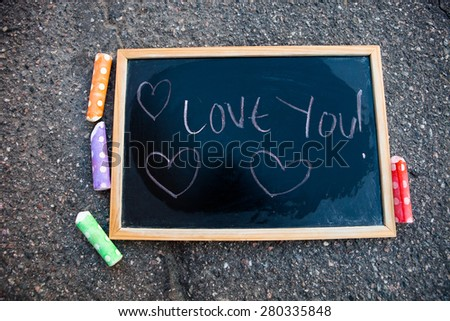 I love you message on chalkboard with hearts and colorful street chalk - stock photo