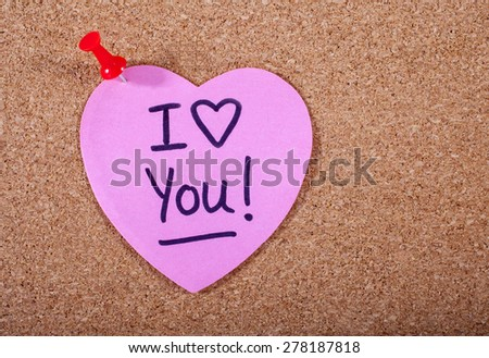 I Love You message written on a heart-shaped piece of note paper. - stock photo