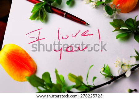 I love you message written on a paper, blossoming twigs around, studio shot
