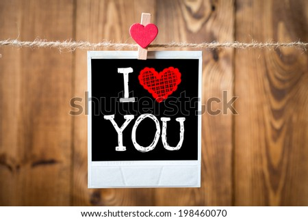 I love You message written on old photo on hanging on rope with wooden wall  - stock photo