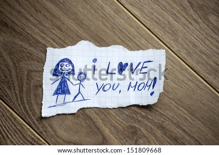 I love you, mom written on piece of paper, on a wood background - stock photo