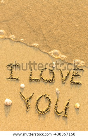 I Love You - text written on sandy beach with shells and the soft wave.
