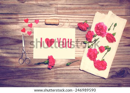 I Love You theme with scissors, twine, and carnation flowers on grungy background - stock photo