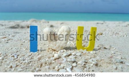 I love you word and coral heart shape with the white sandy beach and blue sky background - stock photo