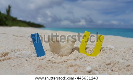 I love you word letters text alphabet on a beautiful romantic white sandy beach - stock photo