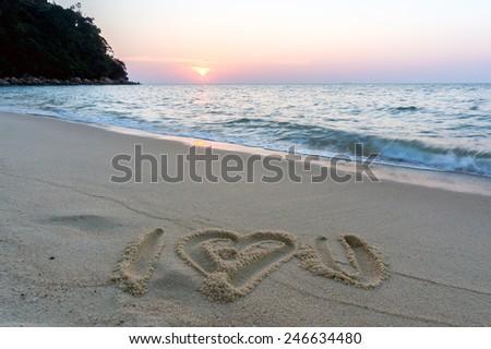 I love you written on sandy beach at sunset - stock photo