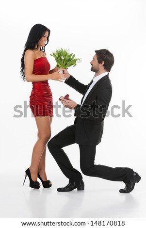 I love you! Young man in full suit standing on one knee and giving a bunch of flowers to his girlfriend while isolated on white - stock photo