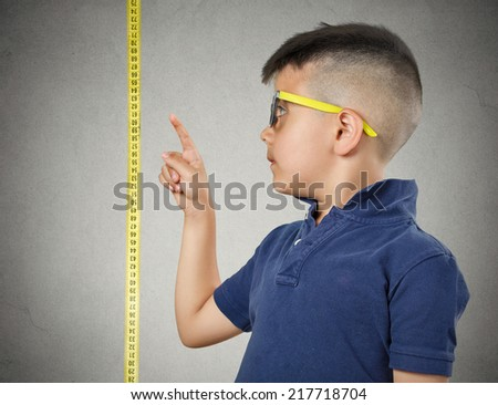 I'm growing up. Child with glasses pointing at his height on measuring tape beside him, grey wall background. Children development concept. Face expression - stock photo
