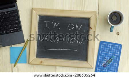 I'm on vacation written on a chalkboard at the office - stock photo