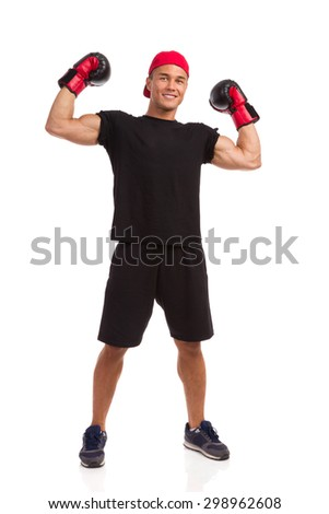 I'm The Winner. Smiling confident muscular man in sport shorts, black t-shirt and sneakers posing with boxing gloves and rising hands. Full length studio shot isolated on white. - stock photo