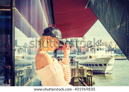 I missing you. American Woman wearing knitted, off shoulder, loose sweater, leather cap, standing by river, looking down, thinking, lost in thought. Boat on background. Instagram filtered effect. - stock photo