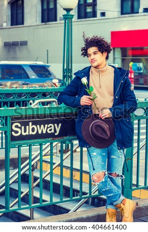 I missing you, waiting you. Wearing jacket with hood, knitted sweater, jeans, holding Fedora hat, white rose, American guy with freckle face, curly hair, standing on street by Subway sign in New York. - stock photo