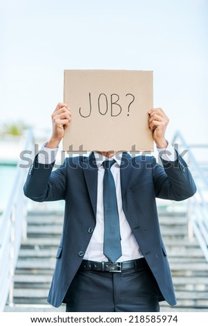 I need a job! Man in formalwear holding poster with job text message in front of his face while standing outdoors and against staircase - stock photo