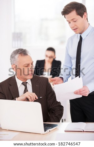 I need an advice. Two confident business people discussing something while on of them pointing paper with woman working on background