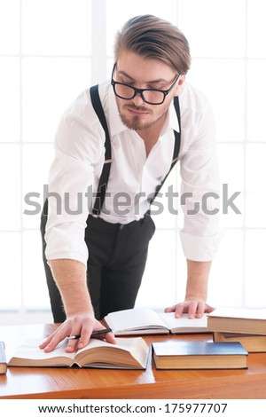I need more information. Thoughtful young man in shirt and suspenders leaning at the table and reading a book laying on it