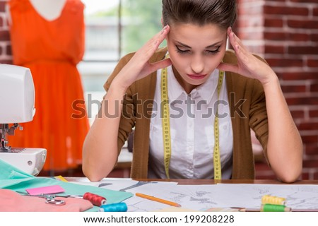 I need some fresh ideas. Tired young woman holding head in hands and looking at fashion sketches while sitting at her working place - stock photo