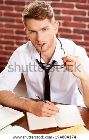 I need some fresh ideas. Top view of thoughtful young man in shirt and tie writing something in note pad and looking away while sitting at his working place - stock photo