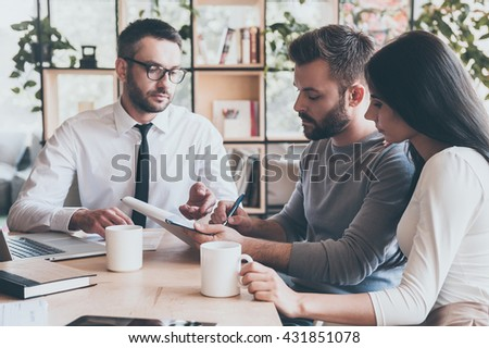 I need your signature. Confident young man signing some document while sitting together with his wife and man in shirt and tie  - stock photo