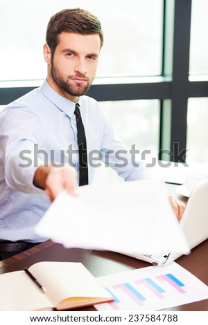 I need your signature here. Handsome young man in shirt and tie stretching out documents while sitting at his working place
