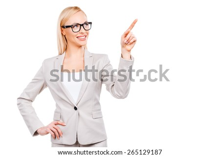 I recommend you this! Confident mature businesswoman pointing away and smiling while standing against white background