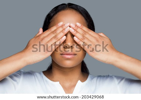 I see nothing. Beautiful young African woman covering eyes with hands while standing against grey background - stock photo
