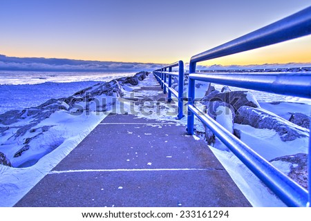 I Walk Alone. A windswept snowy pier along the Great Lakes during a bitter cold winter. Lexington, Michigan.  - stock photo