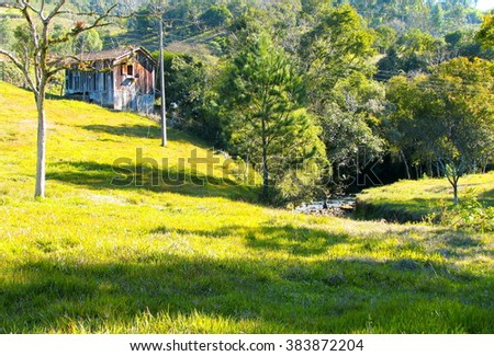 I want a small house on the mountains   A wooden little house with a rocky stream running down through evergreen vegetation, Santa Catarina State, Southern Brazil     - stock photo