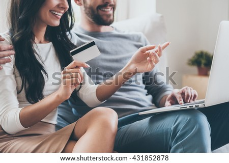 I want this! Close-up of beautiful young woman holding credit card and pointing laptop with smile while sitting together with her husband on the couch  - stock photo