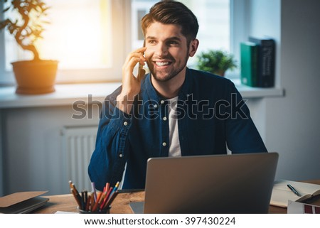 I was waiting for your call! Cheerful young handsome man talking on mobile phone and looking away with smile while sitting at his working place - stock photo